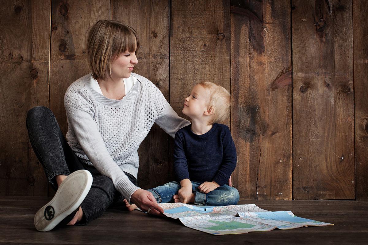 Mutter und Sohn schauen Landkarte an - Deutsches Ferninstitut für Bildung, Pädagogik und Sozialmanagement GmbH