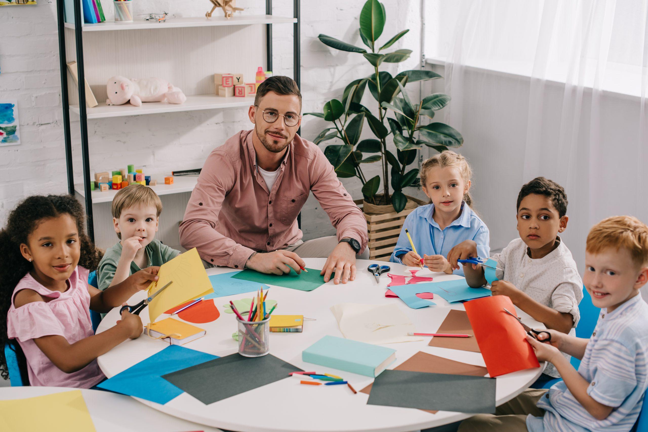 Erzieher sitzt am Tisch mit vielen Kindern - Deutsches Ferninstitut für Bildung, Pädagogik und Sozialmanagement GmbH