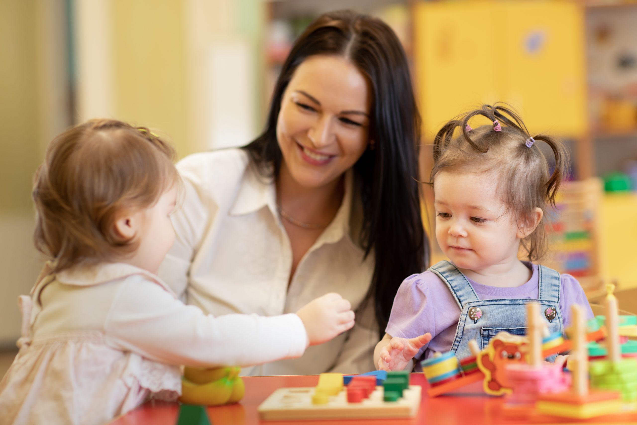 Frau spielt mit 2 kleinen Mädchen am Tisch - Deutsches Ferninstitut für Bildung, Pädagogik und Sozialmanagement GmbH